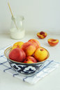 Ripe nectarines in oriental bowl on light background Stock Photo