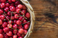 Ripe organic homegrown cherries in a basket on wooden background Royalty Free Stock Photography