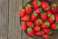 Ripe organic strawberries on dark plate on plank wood background, close up, healthy food, detox Royalty Free Stock Photo