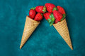 Ripe organic strawberries in waffle ice cream cones, pouring imitation, dark blue background Royalty Free Stock Photo