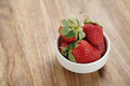 Ripe organic strawberries in white bowl on wood table Royalty Free Stock Photo