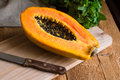 Ripe papaya cut in half on wood cutting board, bunch of fresh mint on rustic kitchen table by window Royalty Free Stock Photo