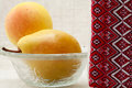 Ripe pears in a glass bowl and towel with ornament Royalty Free Stock Image