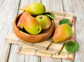 Ripe pears in a wooden bowl with leaves Stock Photos