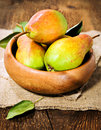 Ripe pears in a wooden bowl on sacking Stock Photos