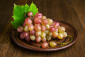 Ripe pink grapes in a clay plate on wooden table Royalty Free Stock Photo