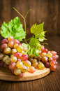 Ripe pink grapes with leaves on a wooden background Royalty Free Stock Photography