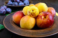 Ripe plums and apricots in ceramic bowls on a dark wooden background Royalty Free Stock Photo