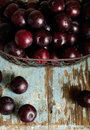 Ripe plums in a basket on a wooden background.