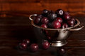 Ripe plums in a colander on a wooden background. Macro photo.