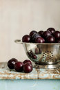 Ripe plums in a colander on a wooden background.