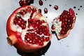 Ripe pomegranate open on mirror surface Stock Photography