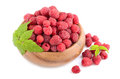 Ripe raspberries red with green leaves in bamboo plate on white background Royalty Free Stock Photos