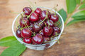 Ripe red cherries with green leaves in a bowl on wooden table closeup Royalty Free Stock Photo