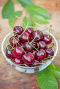 Ripe red cherries with green leaves in a transparent bowl Royalty Free Stock Photo