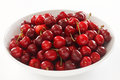 Ripe red cherries in a large white ceramic bowl