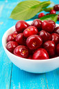 Ripe red cherry berries in a white ceramic bowl on a blue wooden background Royalty Free Stock Photo