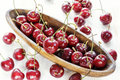 Ripe red cherry with water drops in a wooden elongated plate on an old painted table close up Royalty Free Stock Photo