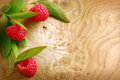 Ripe red raspberries on a woodgrain texture and leaves patterned with copyspace Royalty Free Stock Photography