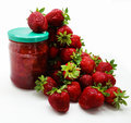Ripe red strawberries and a jar of strawberry jam on a white