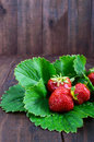 Ripe strawberry among the green leaves on a dark wooden table