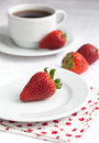 Ripe strawberry on a white plate and a white cup of coffee on a white table Stock Photos