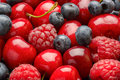 Ripe summer berries (blueberries, raspberries and cherries) as background. Royalty Free Stock Photo