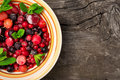 Ripe summer berries with mint in rustic bowl Royalty Free Stock Photo