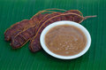 Ripe tamarind and tamarind juice on banana leaf background Stock Photo
