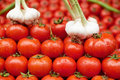 Ripe tomato and garlic for sale red fruits with water drops on market Stock Image