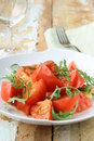 Ripe tomato salad with arugula in a rustic style Stock Photography