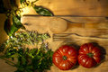 Ripe tomatoes parsley bay leaf and rosemary on kitchen table with wooden spoon fork Royalty Free Stock Photo