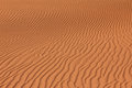 Rippled red brown desert or beach sand texture. Wavy background. Royalty Free Stock Photo