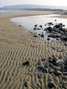 Rippled sand the tide leaves on the shore at shell island gwynedd wales uk Royalty Free Stock Photo