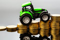 Rising costs in agriculture farmers have to reckon with higher prices for feed fertilizer and plants tractor with coins Royalty Free Stock Photos