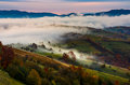 Rising fog covers rural fields in mountains Royalty Free Stock Photo