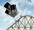Rising oil prices with a group of barrels or steel drum containers in a shopping cart going up on a roller coaster as a Stock Photo