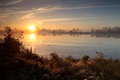 Rising sun over wild lake during misty morning drenthe netherlands Stock Photo