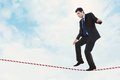Risk in business stock image of businessman walking the tightrope Royalty Free Stock Image