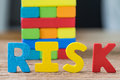 Risk concept with colorful wooden alphabets RISK and wooden bloc