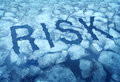 Risk and danger as a thin ice concept with the word embedded in a cracked frozen lake warning any person to be very cautious as a Royalty Free Stock Image