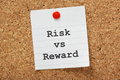Risk vs reward the phrase typed onto a piece of lined paper and pinned to a cork notice board Royalty Free Stock Image