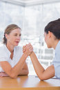 Rival businesswomen having an arm wrestle in their office Stock Photos
