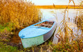 River and blue rowing boat autumn on yellow grass Stock Images