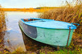 River and boat autumn blue rowing on yellow grass Stock Photo