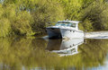 River boat moving up on flat water with spring willow trees in the background Stock Photography