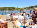 River dart dartmouth devon tourists eating alfresco and enjoying the sunshine on the banks of the at england uk Royalty Free Stock Photo
