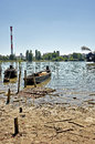 River and industrial zone summer day at with two old fishing boats behind Stock Photography