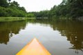 River kayak paddling on through woods horizontal format Royalty Free Stock Photo