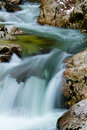 River rocks in smooth satin water flow of waterfall in wintertime Royalty Free Stock Photo